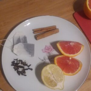 A plate with cinnamon sticks, orange and lemon segments, a small pile of cloves, and tea bags.