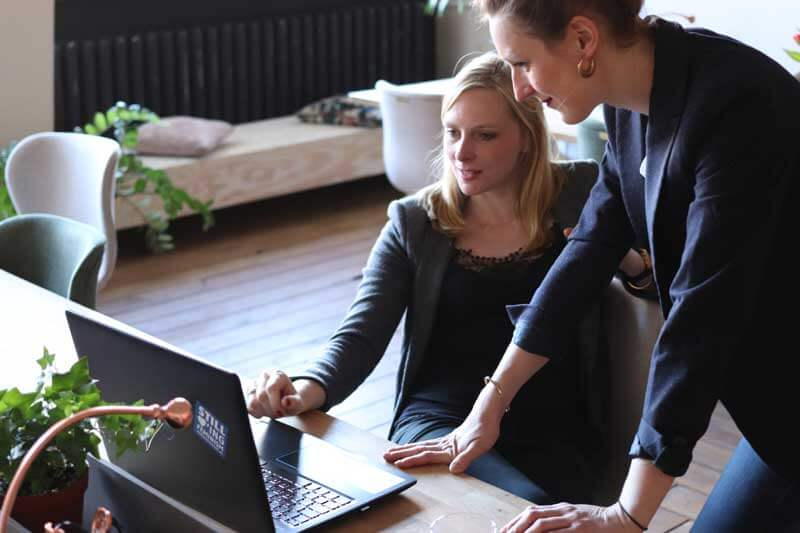 Female employee showing female boss something on computer