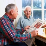 Two senior men enjoying coffee and a newspaper.