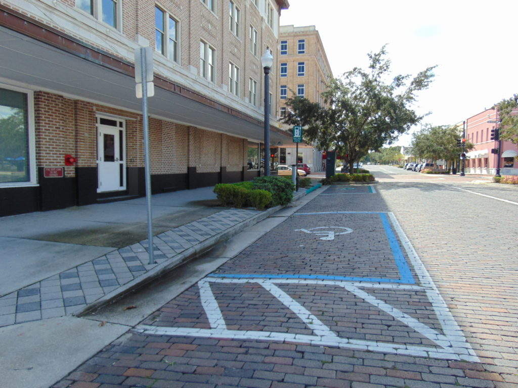Non-Accessible on street parallel  parking space.  The access aisle leads to a raised curb.. Downtown urban renewal.