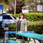 ADA Inspector Susan Berry discovering picinic tables in an Accessible parking space-pointing to accessible parking sign