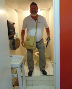 Tom Berry, ADA Consultant. ADA Inspector in a non compliant public restroom. Inspections for ADA Compliance.