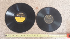 On the left is an LP or Vinyl Record. On the right is a 78 Record. Penny and tape measure used for comparison.