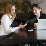 Two young caucasian women meeting, talking, sitting at the table looking in document file or cafe menu, working together beside laptop, copy space