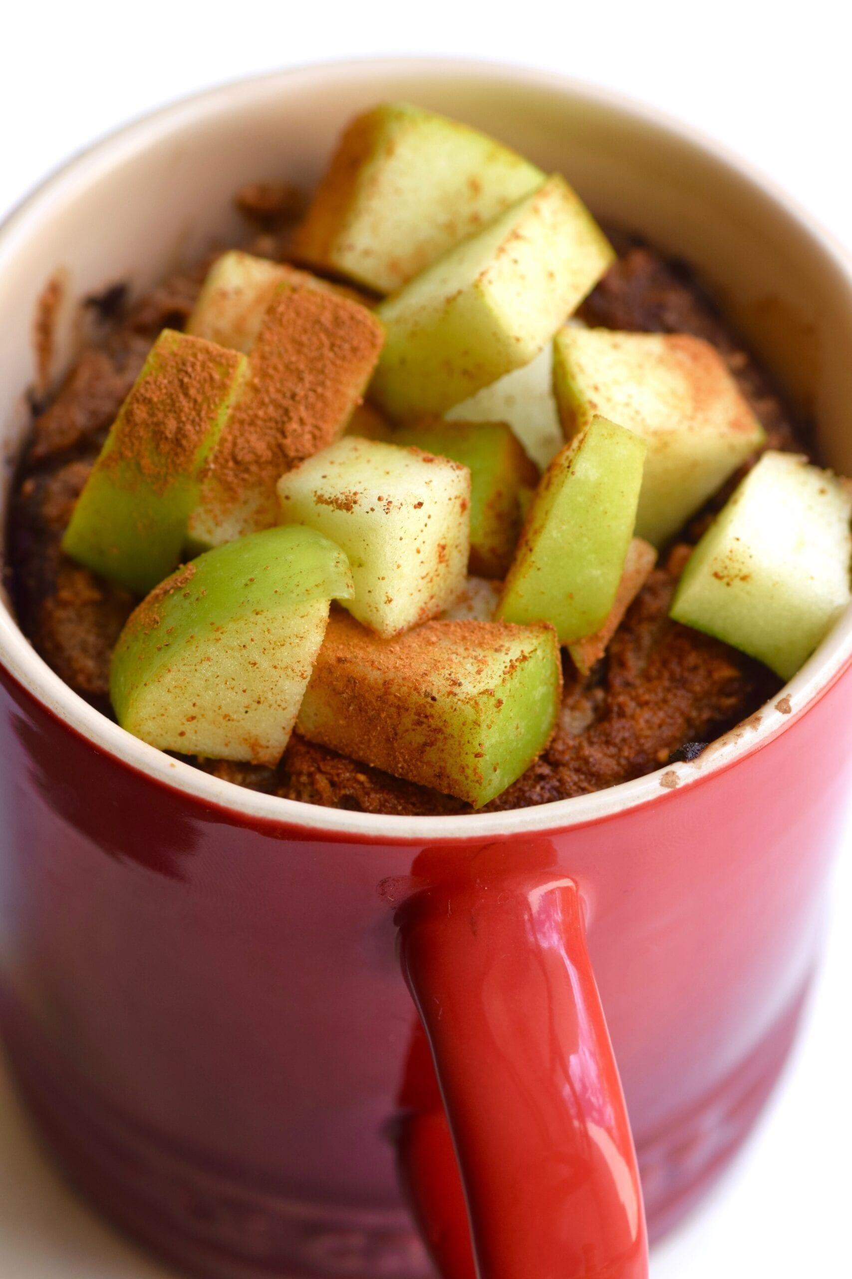 Vegan apple pie mug cake topped with extra apple cubes and cinnamon
