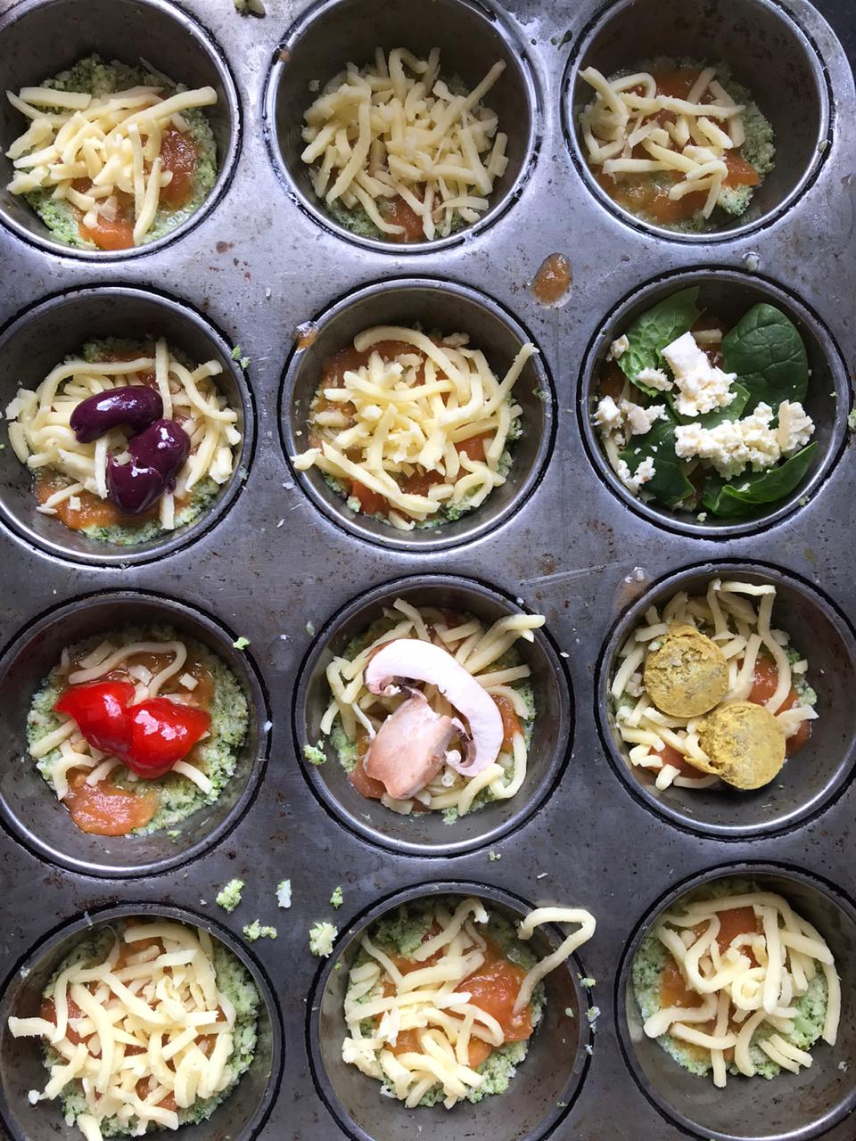 Adding toppings to cauliflower pizza in muffin tin