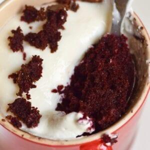 Healthy red velvet cupcake mug cake with spoon inside