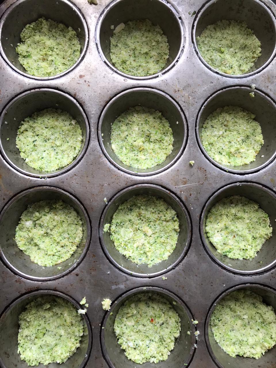 Placing mini cauliflower pizza dough into muffin tin