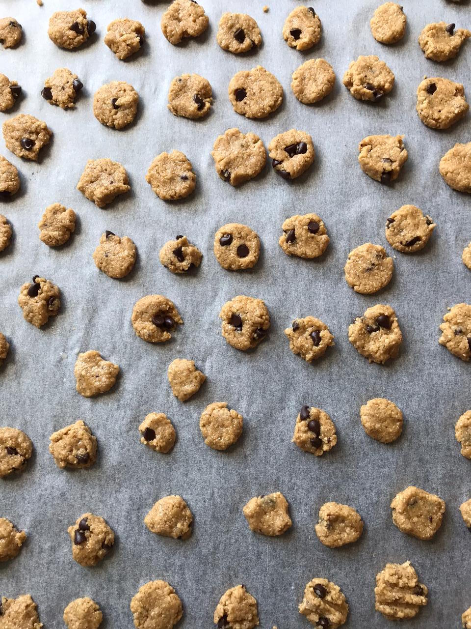 Rolling mini cookie dough balls onto a baking tray