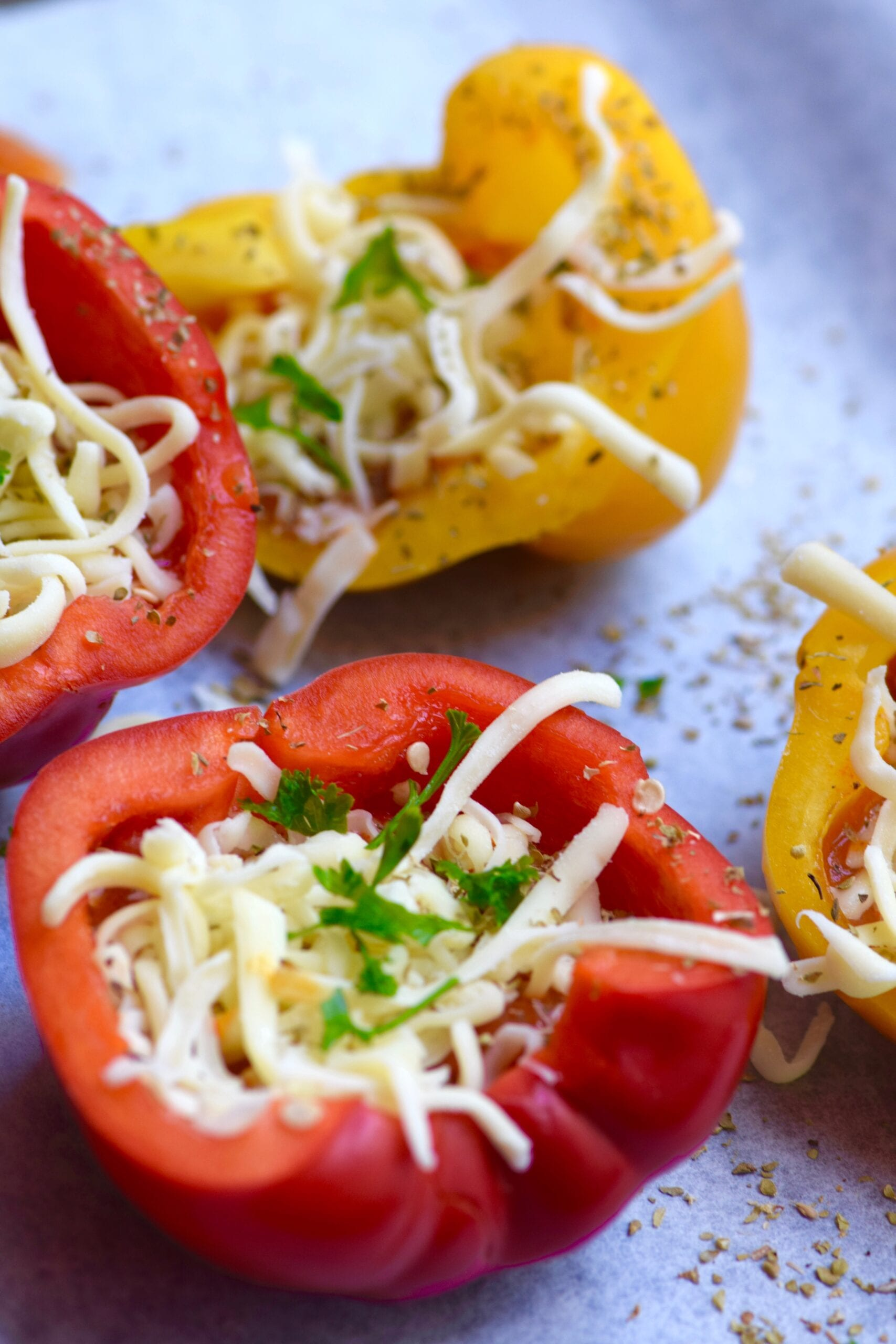 Adding cheese, tomato and spices to the bell peppers