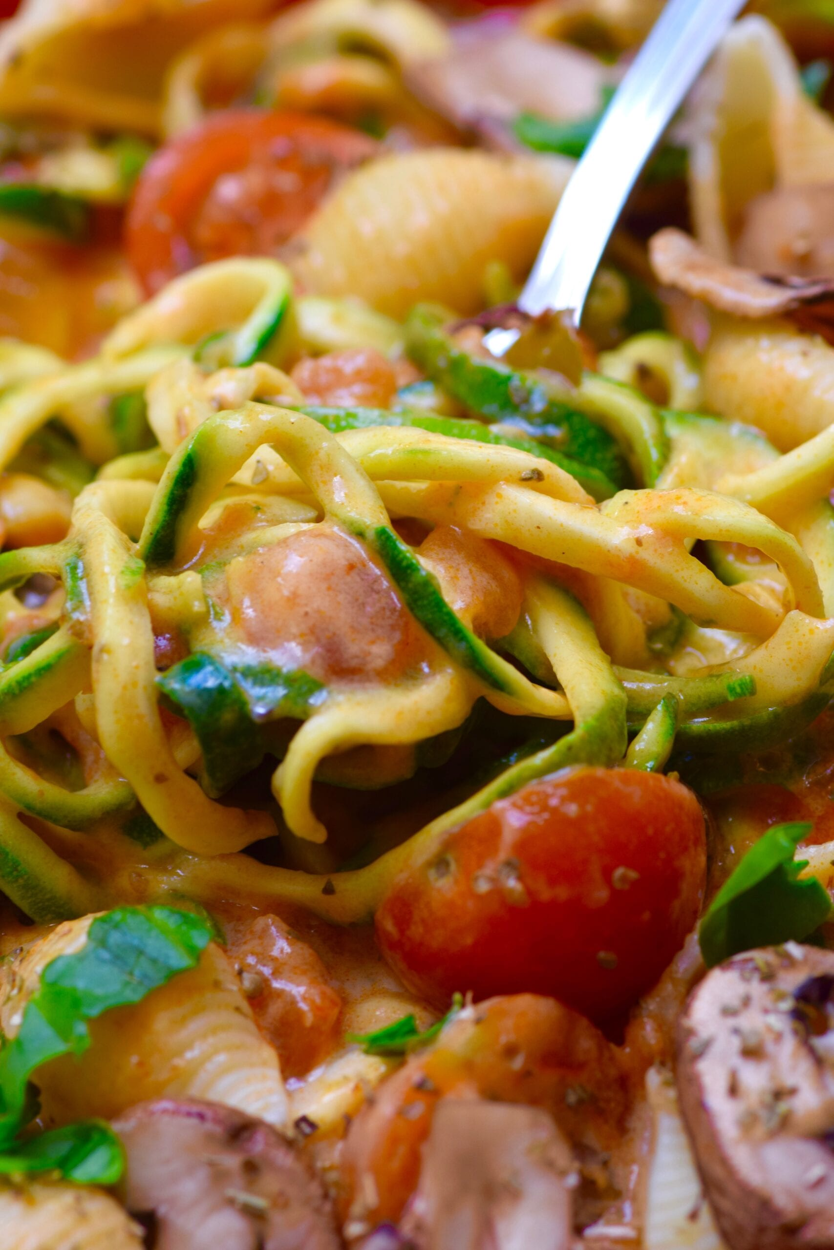 Creamy zucchini tomato pasta with a fork inside