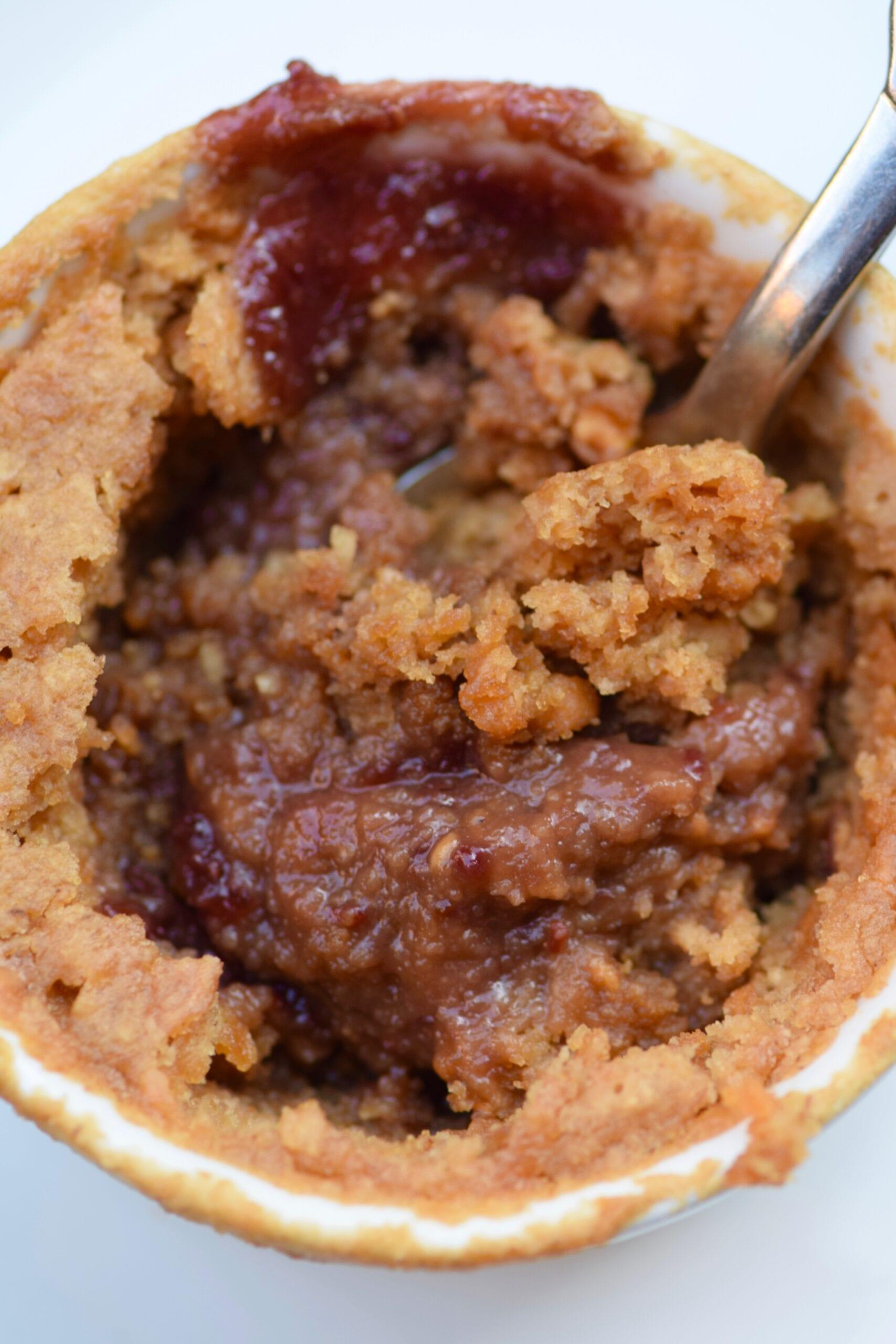 Peanut butter & jelly mug cake with spoon inside it