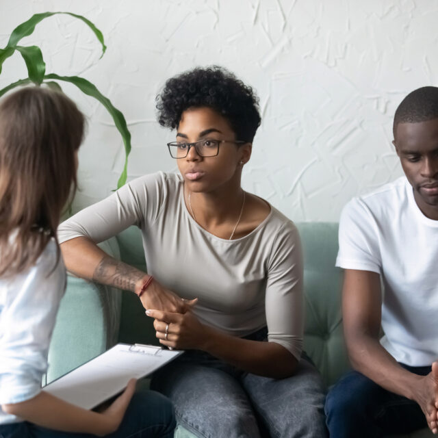 African American millennial couple sit at couch talk with family relationships expert trying to save marriage, unhappy black husband and wife consult with psychologist having relations troubles