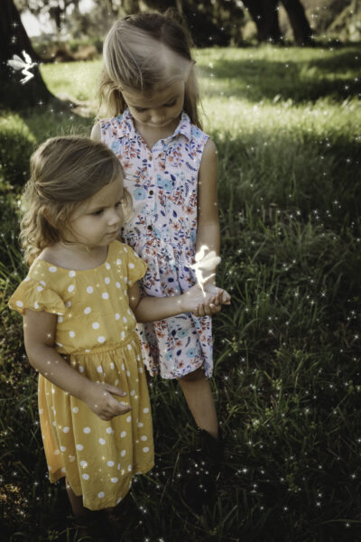 Two Little Girls playing with a fairy