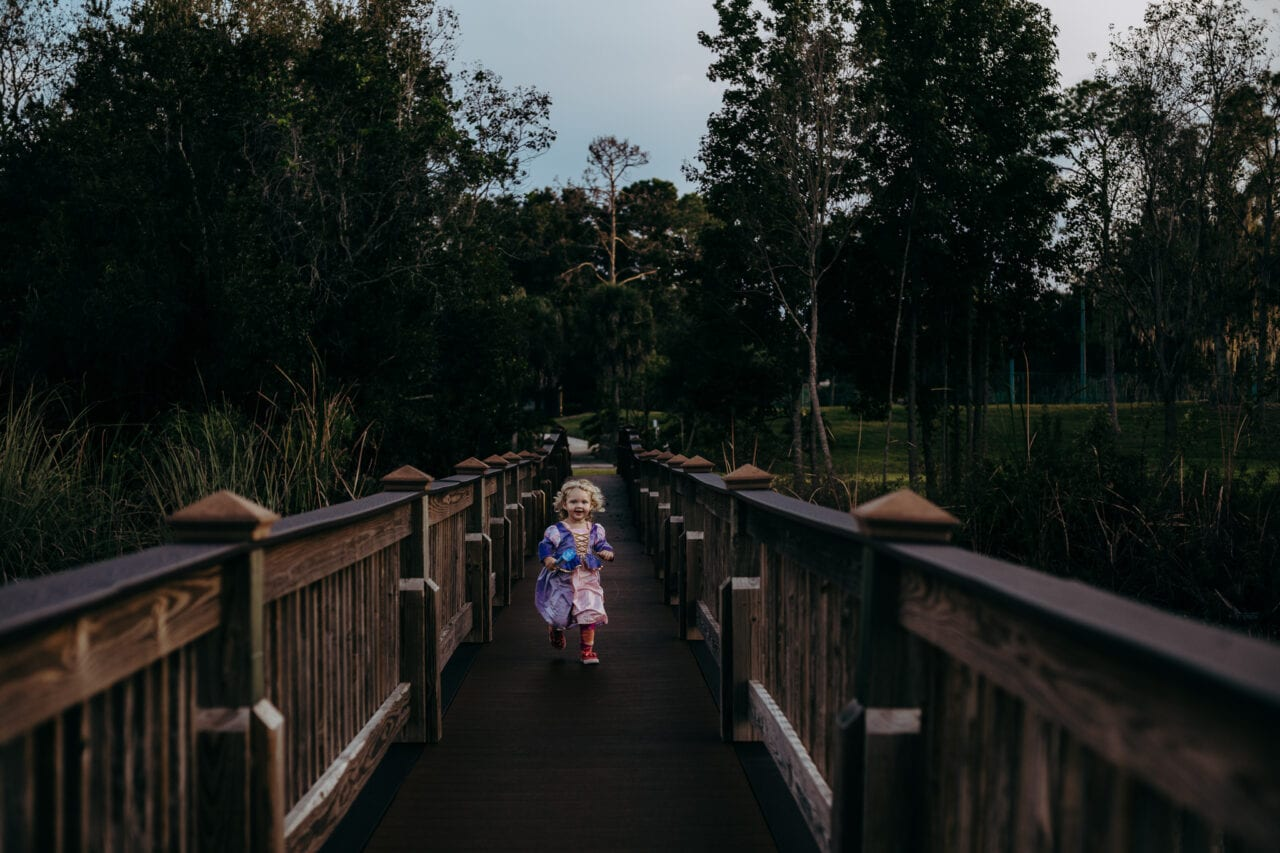 Toddler girl running on bridge