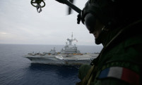 A French navy helicopter crew member looks on as he flies over an aircraft carrier as part of NATO's military operations in Libya