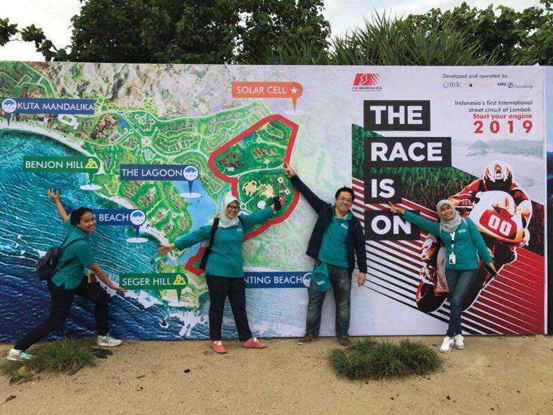 ITDC employees pose in front of Mandalika Race Is On signage heralding new Moto GP race track