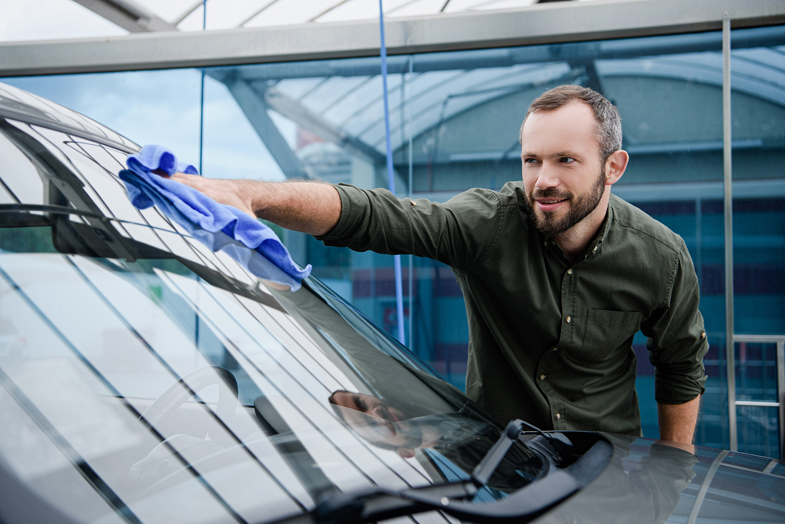 Man wiping the car wind shield with a cloth.