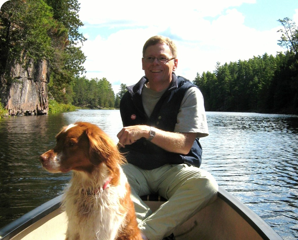 The author paddles his canoe along a river, with a beautiful Brittany Spaniel sitting up in the canoe.