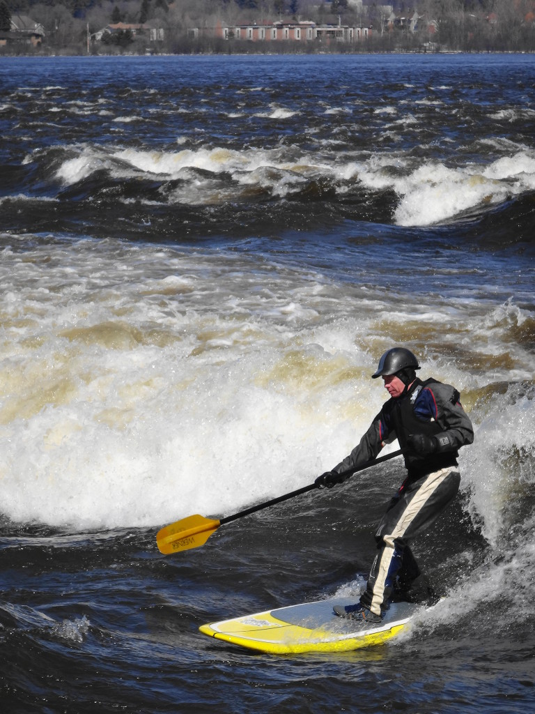 "A stand-up paddleboarder takes his place on the ""The Wave"".  More whitewater lies in the midground of the photograph, while the Quebec shoreline lies in the background."