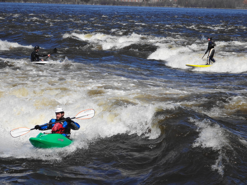 A kayaker and stand-up paddleboarder ride the whitewater at Bate Island