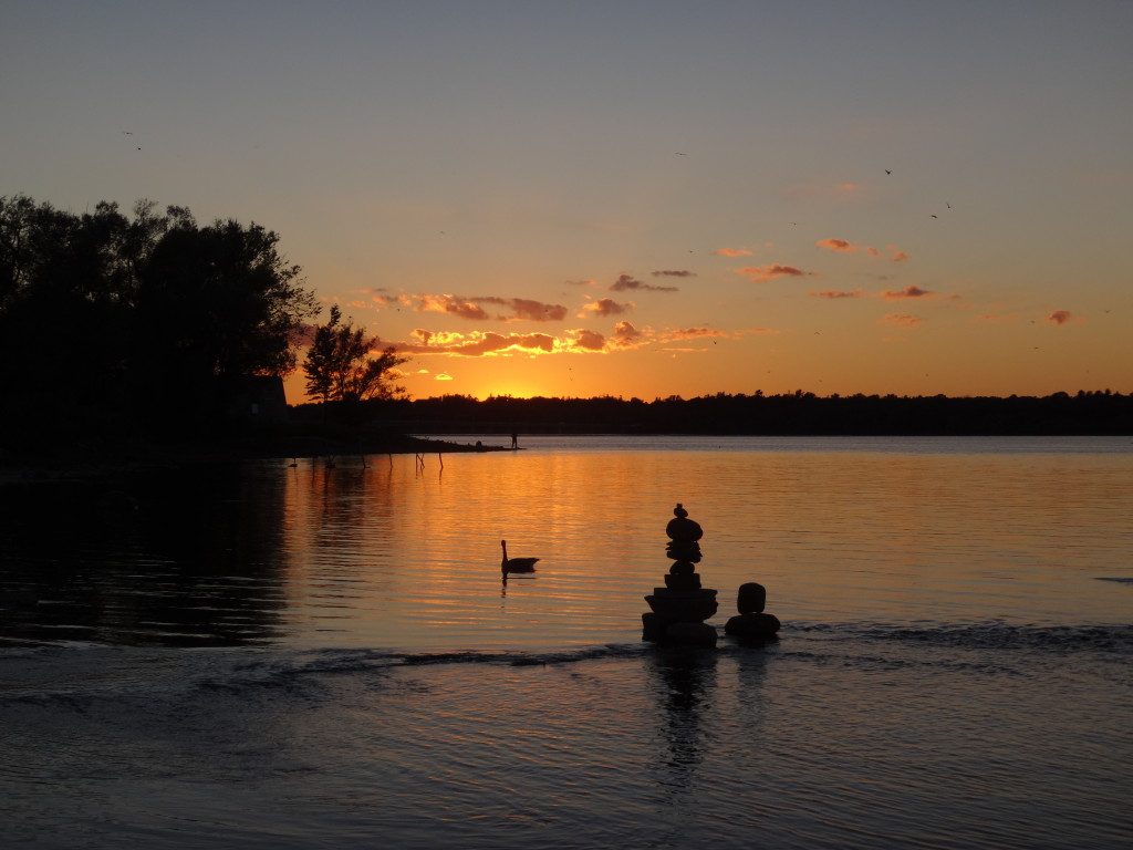 A small balanced rock sculpture is silhouetted against the apricot glow of dusk on the Ottawa River.