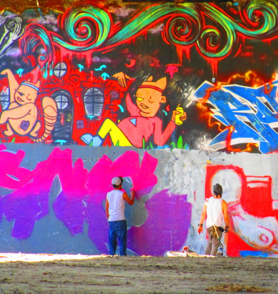 Two artists work on the graffiti wall at the House of PainT under the Dunbar Bridge.