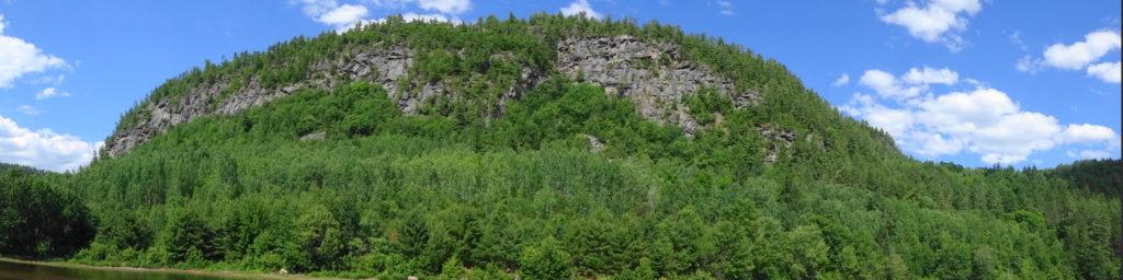 A wide angle photograph shows the towering rock face above Baie de la Presqu'ile d'en Bas.