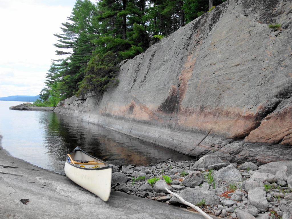 A canoe rests on a rocky shore in a small cove under a flat wall of stone.