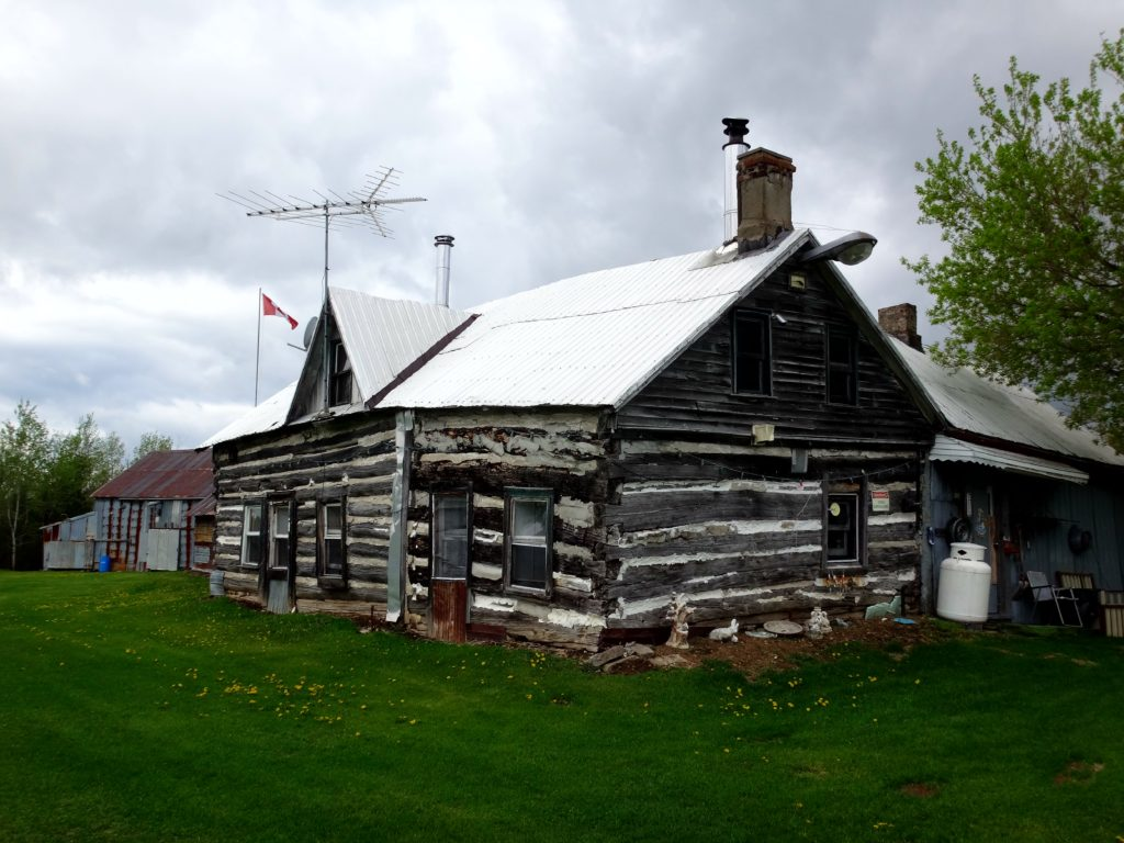 A city-owned, heritage log farmhouse lies under a grey sky on a farm in the Marlborough Forest.