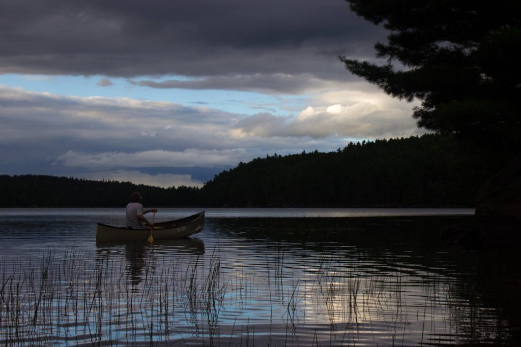 The author paddles his canoe across St. Andrew's Lake in the dusk.
