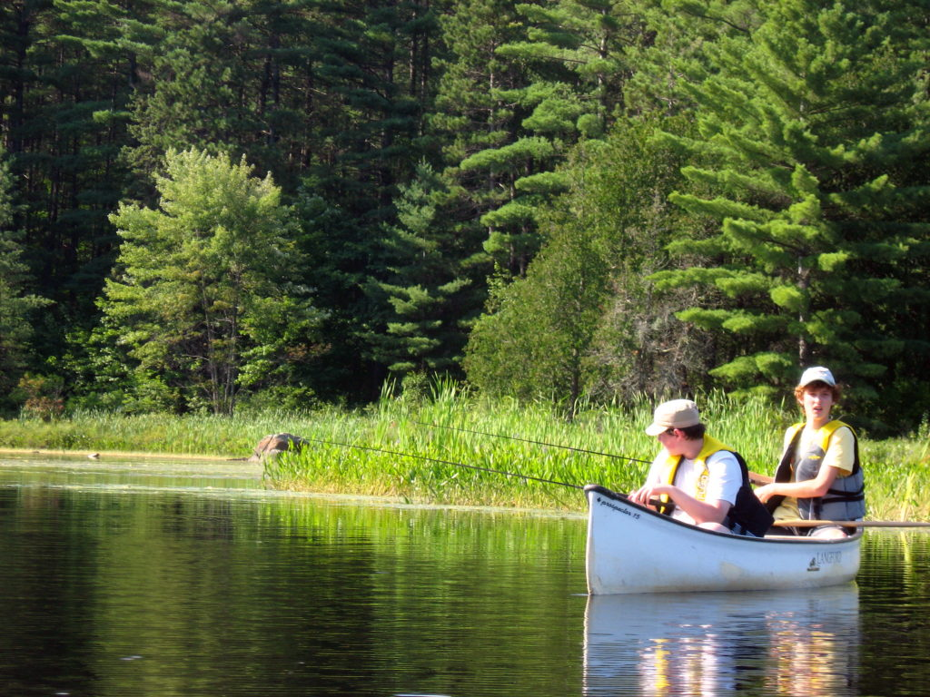 Two teenagers fish from a canoe in Algonquin Park.