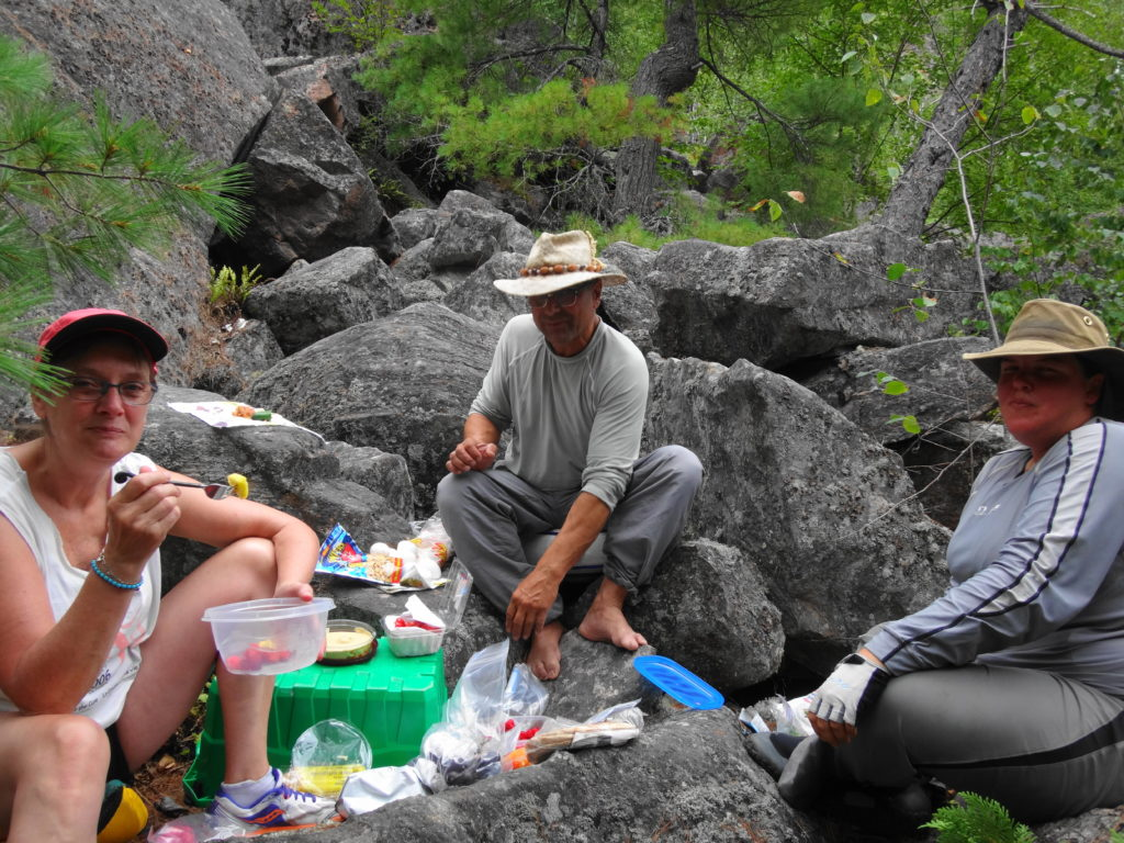 Friends share a lunch on boulders deep in the Barron Canyon.
