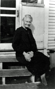 Margaret Ann (Bruegger) Kienlen, ca. 1938, is seated on back steps of a house.