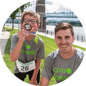 A boy posing with his race medal next to a smiling program coordinator