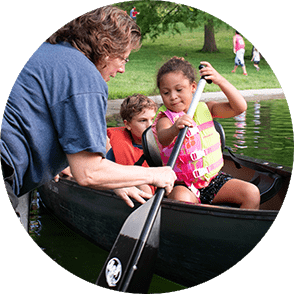 A woman helping a little girl push off in a canoe