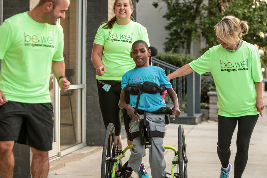 A boy in a wheelchair is joined on a walk by a group of smiling adulys