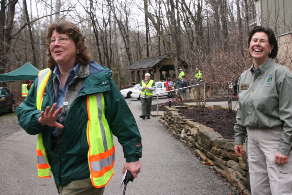 Erin Morris and naturalists smiling and directing traffic at an event