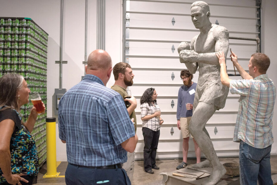 A group of people stand around watching a man sculpting a towering clay statue of a boxer