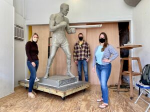 Three people posing with the Ezzard Charles statue