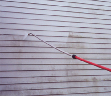 Pressure wash cleaning the siding of house