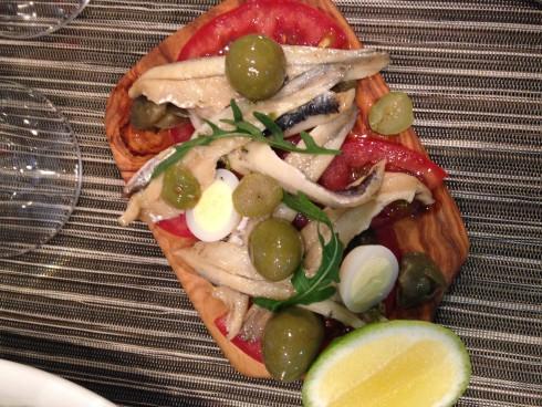 White anchovies, quails egg, manzanilla olives & tomato salad, caper dressing at Terra del Capo tapas restaurant.