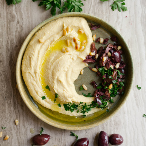 Creamy hummus with olive oil, pine nuts, parsley & crushed olives (photography by Tasha Seccombe)
