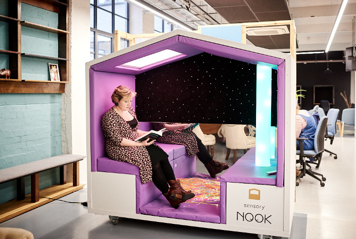 Woman sat in Nook Sensory Sanctuary in a workplace, reading a book and looking contented.