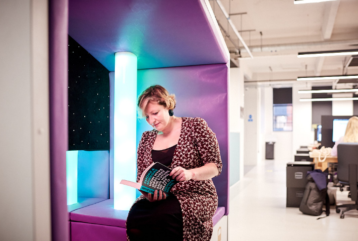 Woman sat in a Nook Sensory pod in an open plan workspace, looking cosy and relaxed reading a book.