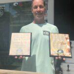 Captain Whitney holding best fishing captain awards