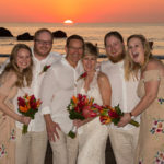 Wedding group in front of an ocean sunset