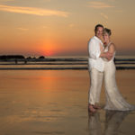 Newly wedded couple in front of an ocean sunset