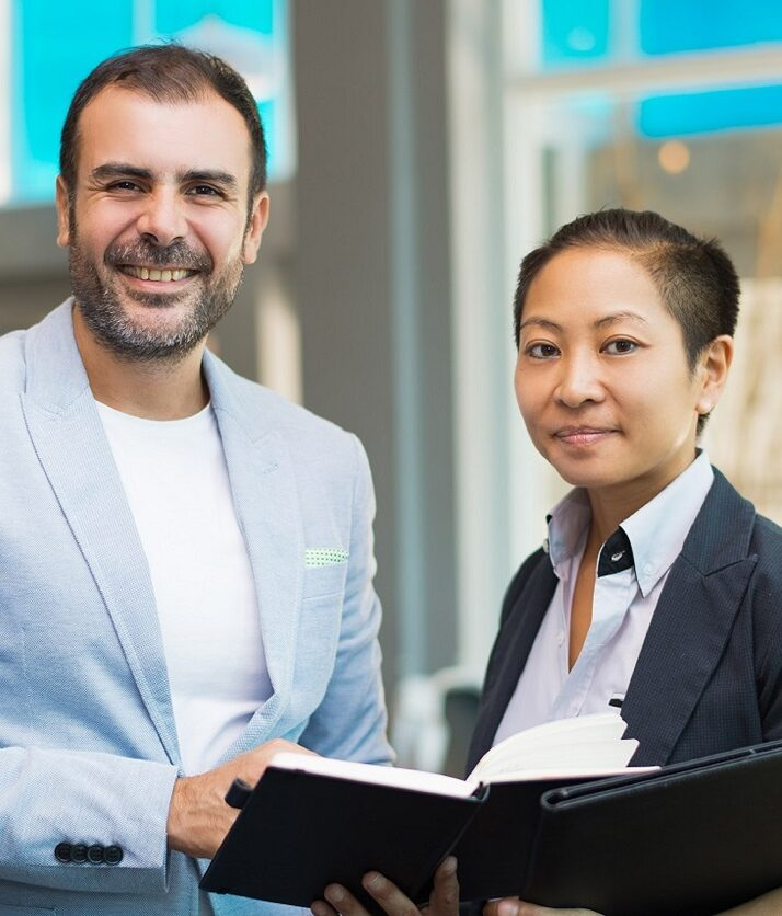 Portrait of successful mid adult leader and his female assistant. Latin American businessman and Asian businesswoman standing together, looking at camera and smiling. Business team concept