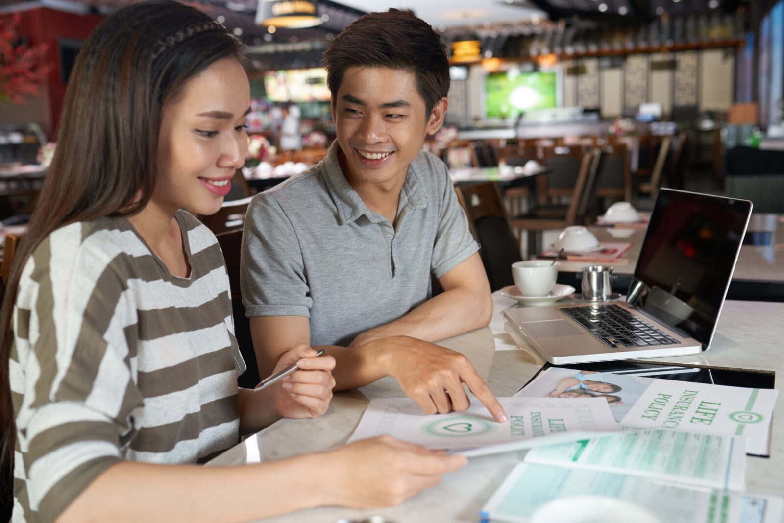 Joyful Asian couple in casualwear sitting at table of spacious cafe and studying details of life insurance policy